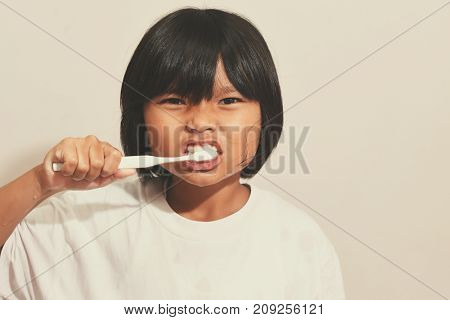 Little girl brushing her teeth in the bathroom