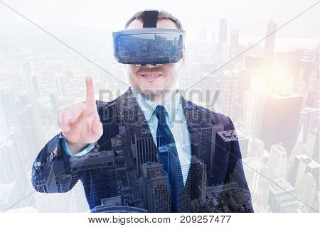 First test. Pleasant bristled man in a business suit wearing a VR headset, testing it and raising his index finger as if ready to press a button with it
