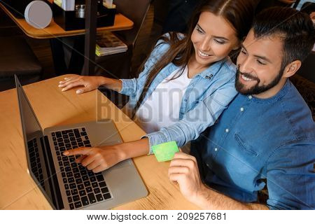 Young couple with laptop and credit card indoors. Internet shopping concept