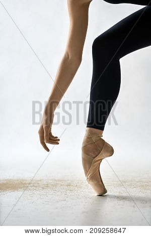 Pretty ballerina is posing in the studio on the light background. She stands on the toe and holds the arm next to the leg. Girl wears black leggings and beige pointe shoes. Closeup. Vertical.