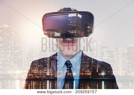Fascinating experience. Close up of a charming bristled young man in a business suit wearing a VR headset and looking at the camera while his image being superimposed on the night city landscape