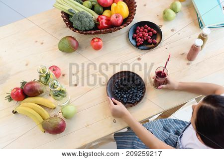 Partial view of woman sitting at wooden table with detox drink in hand and fresh berries on plate