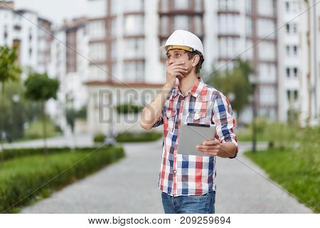 Professional architect in a hardhat holding a digital tablet looking shocked covering his mouth expressively emotionsh surprise shock overwhelming news technology project people business industry