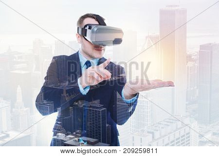 Engrossed in playing. Handsome young man in a business suit wearing a VR headset and interacting with an object in his palm in the virtual reality