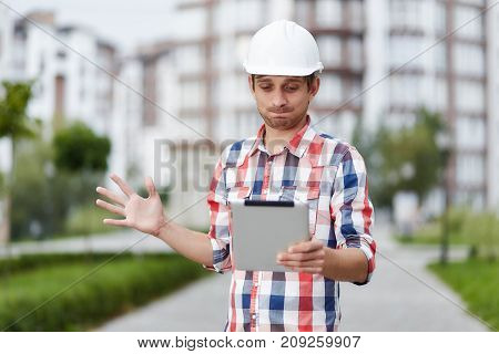 Young male constructionist looking confused and puzzled while browsing on a digital tablet standing in the city in front of apartment buildings. Occupation job career lifestyle engineering