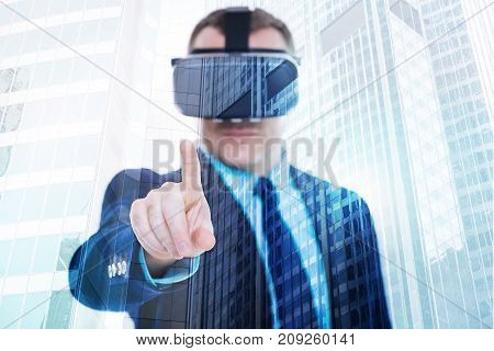 Hey you there. Handsome young man in a business suit wearing a VR headset and pointing with his index finger at the camera while standing against urban background