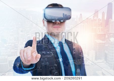 Enjoying technology advances. The focus being on a raised index finger of a handsome young man in business suit wearing a VR headset