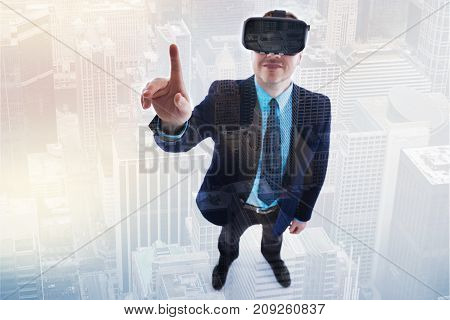 Mood-boosting gaming. Top view of a pleasant young man in a business suit raising his index finger while playing virtual reality games in his VR headset and smiling