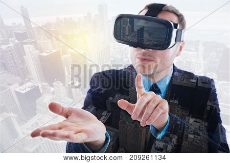 Amusing gaming. Charming bristled man in a business suit using his new VR headset and raising his index finger to touch a virtual object on his palm