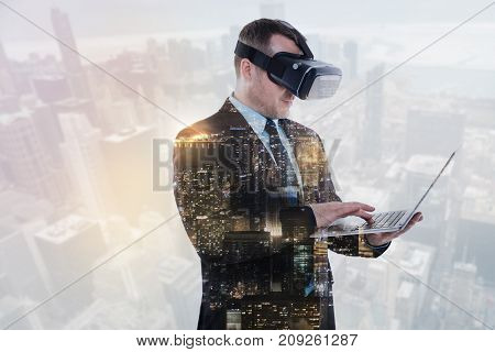 Enhancing user experience. Handsome bristled man in a business suit holding a laptop, typing on it while wearing a VR headset thus improving his user experience