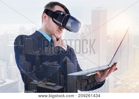 Interesting content. Handsome bristled businessman holding a laptop and reading an article from it while wearing a VR headset for better experience