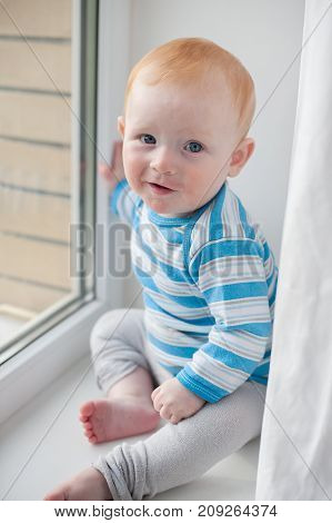 Redheaded baby boy with atopic dermatitis on the window