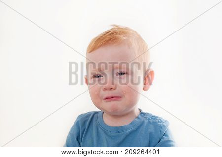 Offended and upset the baby cries on white background