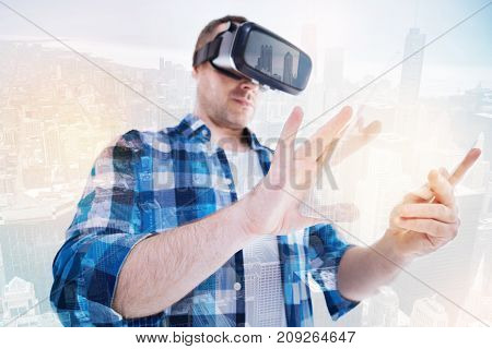 Augmented reality. Stocky middle-aged man using VR headset and working on a transparent tablet zooming in a content visible through VR