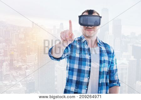 Real-life emulator. Pleasant smiling man wearing a VR headset, playing a game and raising his index finger as if being ready to ring a doorbell