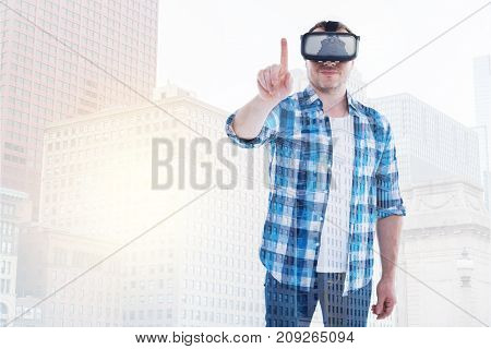 Love technologies. Charming bristled man in a checkered shirt wearing a VR headset and posing in it against an urban background while raising his index finger