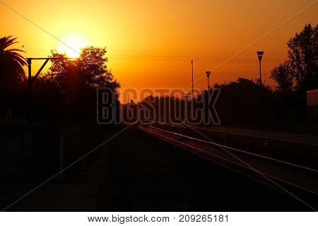 Dawn with the sun appearing on the horizon over the railway