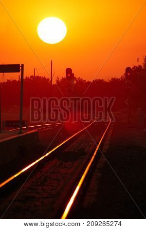 Dawn with the sun appearing on the horizon over the railway with lens flare