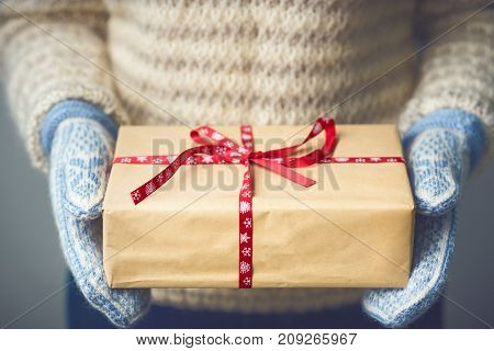 Christmas background. Girl in a warm knitted sweater and mittens is holding a Christmas present. Gifts for men. Merry Christmas. Gift for a girl. Knitted dress. Image is toned in fashionable color.