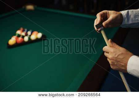 Caucasian Man wipes a cue with chalk ready to start game. Poolroom on the background.