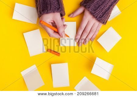 Top view of a hand taking down note in a personal notebook.