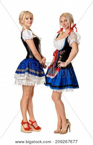 A full length portrait of two beautiful women in a traditional costume isolated on white. Oktoberfest. Beer Festival