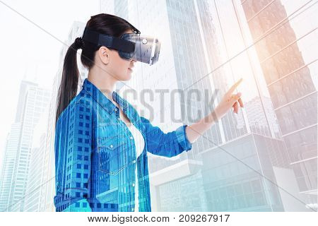 Delicate touch. The side view of a charming young woman raising her hand and touching a virtual object with her index finger while playing a VR game