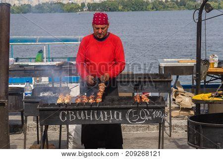 Dnipro Ukraine - September 10 2017: Man cooking Georgian shashlik on a Dripro river embankment during City Day local activity