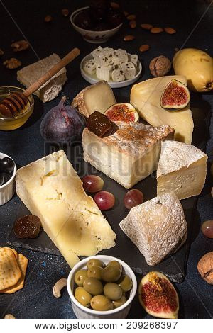 Food Composition With Blocks Of Moldy Cheese, Pickled Plums, Honey, Grape Bunch, Olives, Figs, Crack