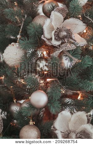 Group of silver and gold vintage Christmas toys weigh on green branches Christmas tree closeup