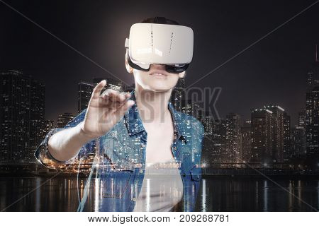 Getting closer. Pleasant young woman playing a VR game and putting her hand forward in a attempt to touch an object in front of her while standing against a night city background