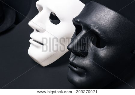 White and dark human masks isolated on black background