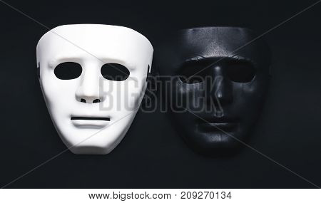 White and dark human masks isolated on black background