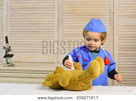Boy In Surgical Uniform Holds Syringe On Wooden Background.