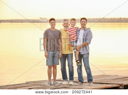 Cute boy with brother, daddy and grandfather standing on pier