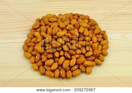 Orange beans heap on wooden planks background