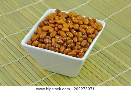 Yellow beans in white bowl on bamboo mat