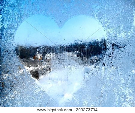 heart form snowflakes ice pattern with sunlight on winter window glass