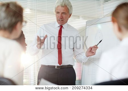 Mature policeman standing by whiteboard and explaining some data or evidence