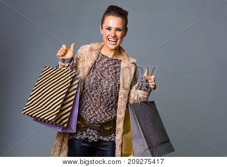 Woman Isolated On Grey With Shopping Bags Showing Thumbs Up