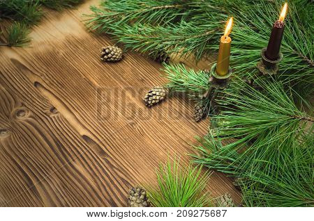 Fir tree branches with scattered cones around and candles in vintage candleholder on brown wooden table surface background with copy space. Christmas table decoration.