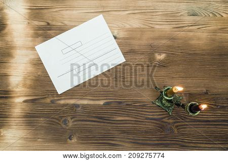 Envelope letter on wooden table surface background with copy space in the light of candles in retro candle holder.
