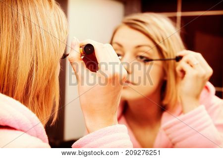 Blonde Woman Wearing In Dressing-gown Applying Mascara In Mirror At Home