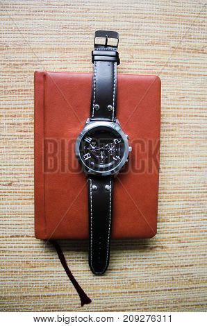 Wrist watch on the notebook to start work
