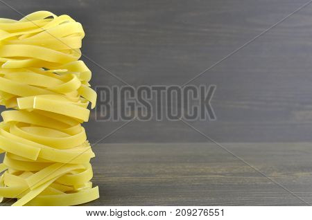 Tagliatelle raw yellow pasta on wooden background
