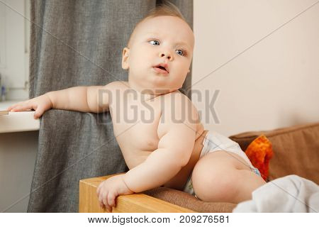 Innocent infant with perfect skin sits on the sofa and holds one hand on window sill. Adorable newborn child in pants with wide open mouth