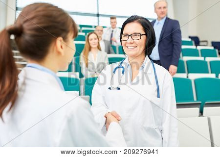 Doctors congratulate woman with handshake for successful career test results