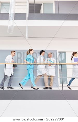 Team of doctors have emergency and run in hospital hallway