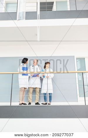 Team of doctors on clinic hallway discuss patient therapy