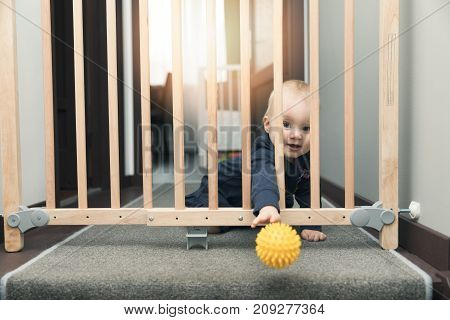 child throwing ball away through safety gates in front of stairs